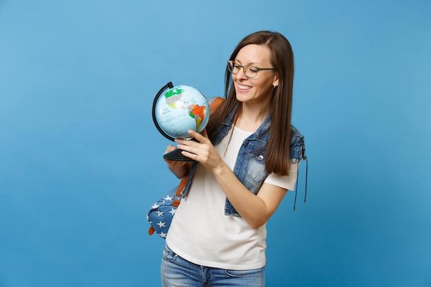 Portrait d'une jeune étudiante souriante séduisante dans des verres avec sac à dos tenant un globe terrestre et apprenant la géographie isolée sur fond bleu. éducation dans le concept de collège universitaire secondaire.
