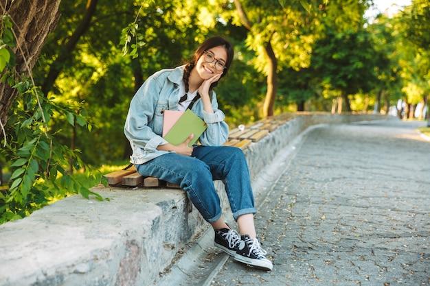 Portrait d'une jeune étudiante souriante et souriante portant des lunettes, assise sur un banc à l'extérieur dans un parc naturel tenant des livres.