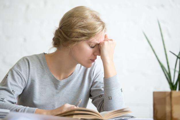 Portrait d'une jeune étudiante surchargée de travail assise à la table