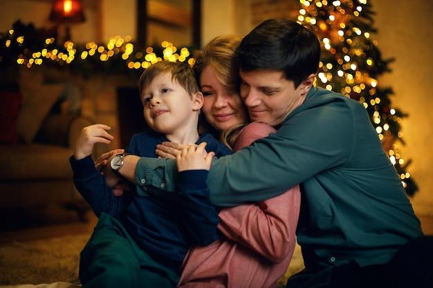 Portrait de jeune famille caucasienne étreignant avec leur enfant posant sur le sol dans un intérieur de noël confortable