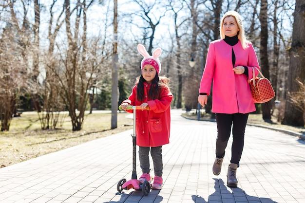 Portrait de jeune famille caucasienne, marchant le long de la rue, petite fille avec scooter