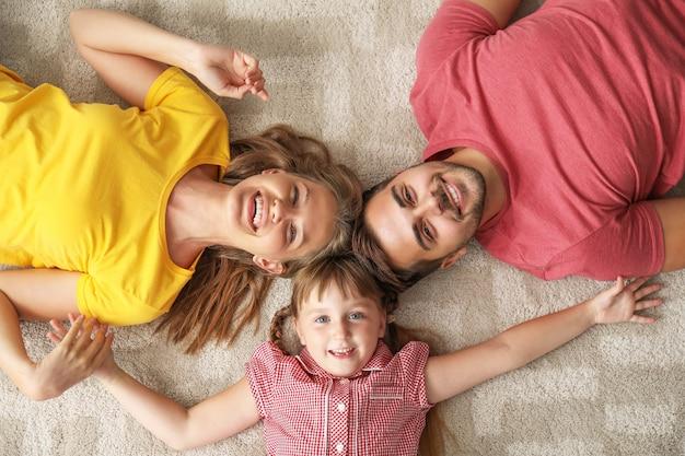 Portrait de jeune famille heureuse allongée sur un tapis à la maison
