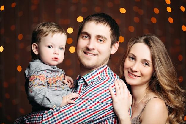 Portrait de jeune famille heureuse assis ensemble