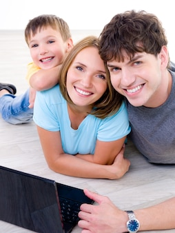 Portrait de jeune famille heureuse en riant avec petit fils et avec ordinateur portable - à l'intérieur