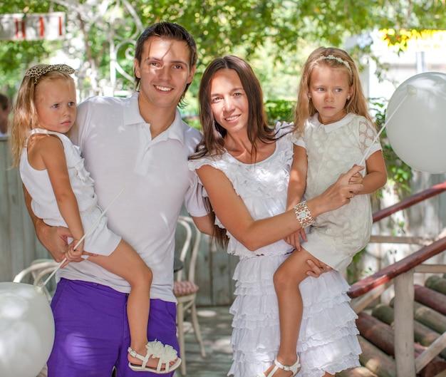Portrait jeune famille de quatre personnes au café avec ballons blancs