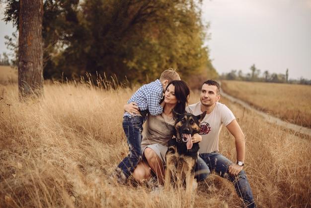 Portrait d'une jeune famille qui joue avec un chien sur la nature l'après-midi d'automne