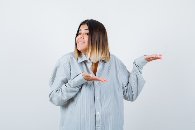 Portrait de jeune femme accueillant quelque chose en chemise surdimensionnée et à la vue de face heureuse