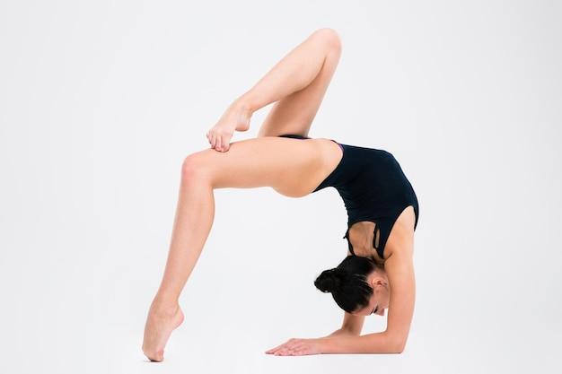 Portrait d'une jeune femme acrobate qui s'étend isolé sur un mur blanc