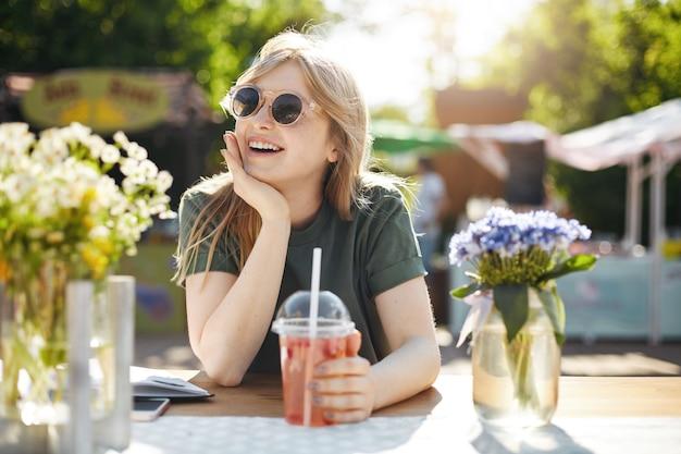 Portrait de jeune femme adorable boire de la limonade dans le parc entouré de flowes