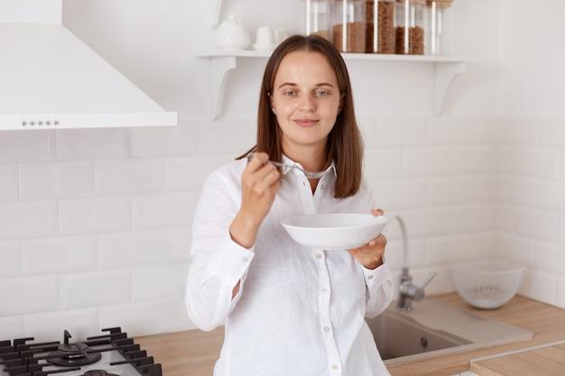 Portrait d'une jeune femme adulte séduisante souriante aux cheveux noirs vêtue d'une chemise décontractée blanche, prenant son petit-déjeuner dans la cuisine, tenant une assiette dans les mains, regardant la caméra avec une expression agréable.