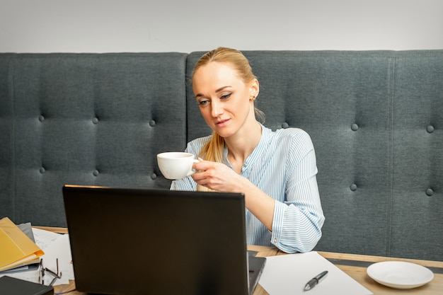 Portrait d'une jeune femme d'affaires à l'aide d'un ordinateur portable assis à la table avec une tasse de café dans un café