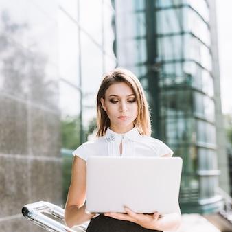 Portrait de jeune femme d'affaires à l'aide d'un ordinateur portable