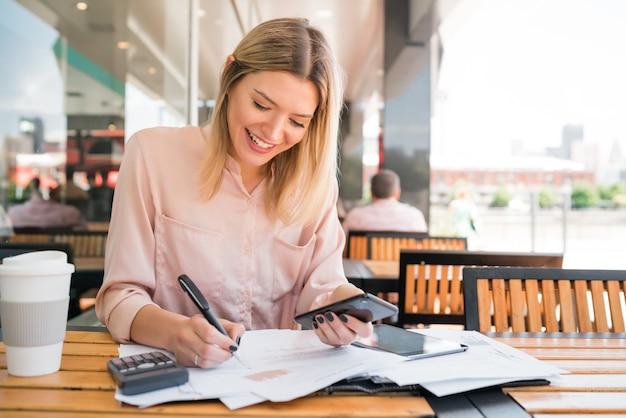 Portrait de jeune femme d'affaires à l'aide de son téléphone portable tout en travaillant au café. concept d'entreprise.