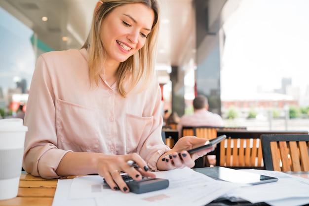 Portrait de jeune femme d'affaires à l'aide de son téléphone portable tout en travaillant au café-restaurant. concept d'entreprise.