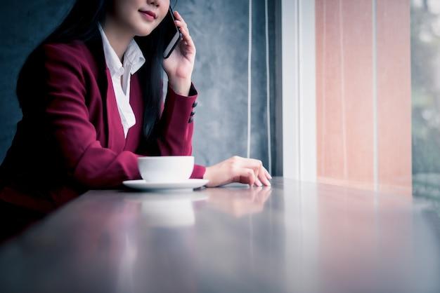 Portrait de jeune femme d'affaires asiatique assis à l'intérieur dans un café, boire du café à l'aide d'un téléphone intelligent. concept de réussite commerciale.