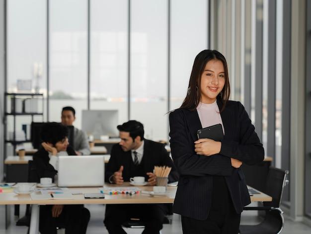 Portrait d'une jeune femme d'affaires asiatique confiante souriante et tenant une tablette dans un bureau de travail, leadership féminin, concept d'analyse et de stratégie d'entreprise, pouvoir de la jeune génération