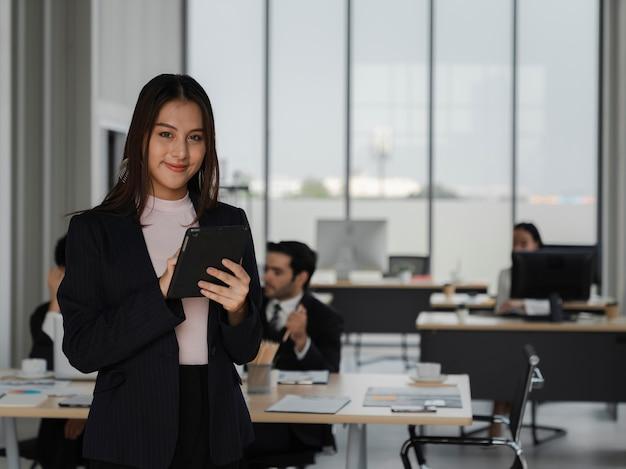 Portrait d'une jeune femme d'affaires asiatique confiante tenant une tablette et souriante dans un bureau de travail, leadership féminin, analyse commerciale et concept stratégique, pouvoir de la jeune génération, travail heureux