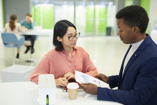 Portrait jeune femme d'affaires asiatique discutant des documents de travail