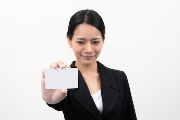 Portrait de jeune femme d'affaires asiatique souriante tenant carte de crédit vide isolé sur fond gris