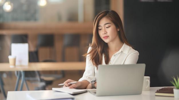 Portrait de jeune femme d'affaires asiatique travaillant sur son projet avec un ordinateur portable dans un bureau moderne