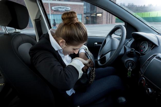 Portrait de jeune femme d'affaires assise sur le siège du conducteur et regardant à l'intérieur du sac à main