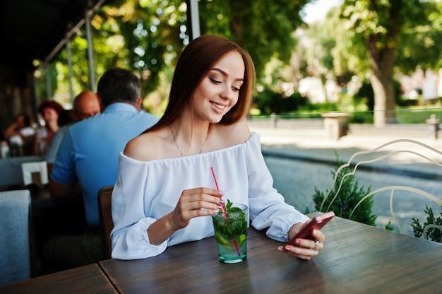 Portrait d'une jeune femme d'affaires attrayante avec un cocktail mojito envoyer un sms sur son smatphone.