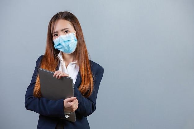 Portrait de jeune femme d'affaires belle portant un masque facial sur une surface grise