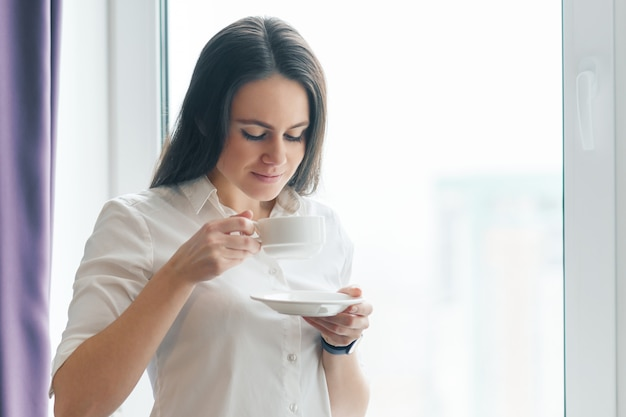 Portrait de jeune femme d'affaires en chemise blanche avec une tasse de café