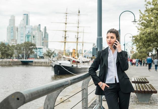 Portrait, jeune, femme affaires, conversation, sur, téléphone portable, penchant, près, les, balustrade