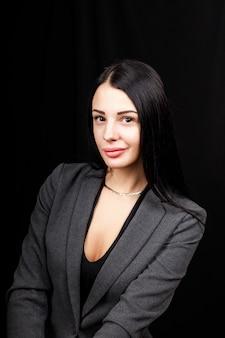 Portrait de jeune femme d'affaires dans une veste grise sur fond noir.