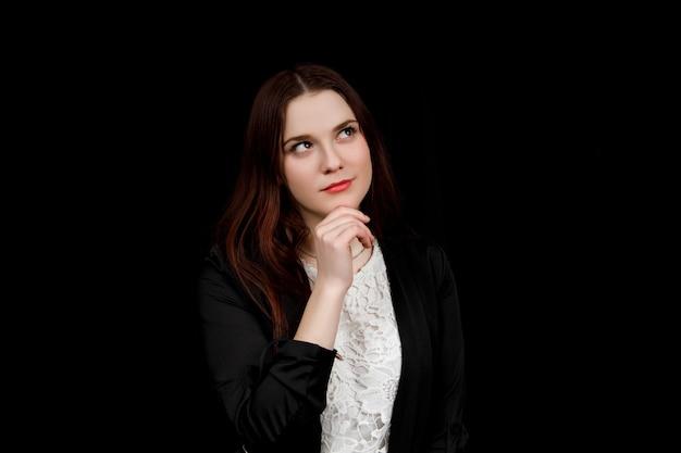 Portrait de jeune femme d'affaires dans une veste noire pense