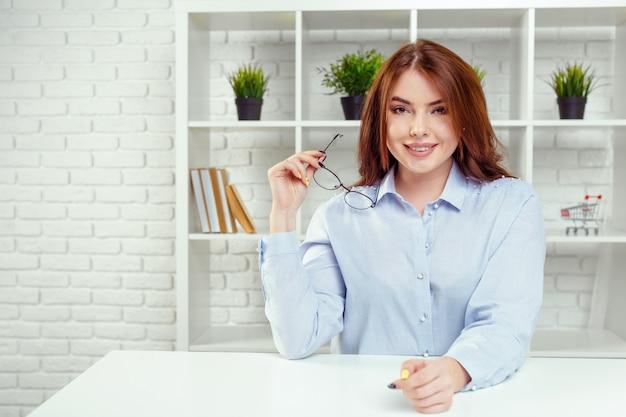 Portrait de jeune femme d'affaires gai sourire heureux au bureau