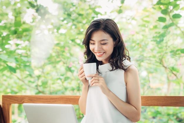 Portrait d'une jeune femme d'affaires heureuse avec une tasse dans les mains, buvant du café et regardant sur un ordinateur portable.