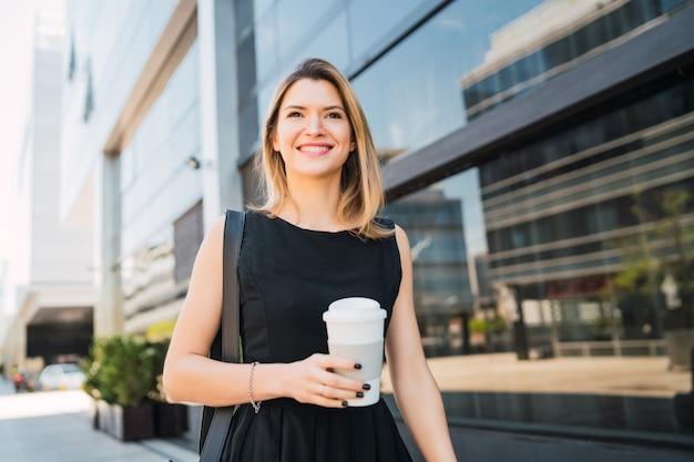 Portrait de jeune femme d'affaires marchant au travail tout en buvant du café à emporter