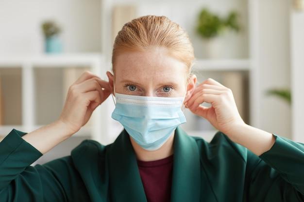 Portrait de jeune femme d'affaires mettant le masque tout en travaillant au bureau post pandémie