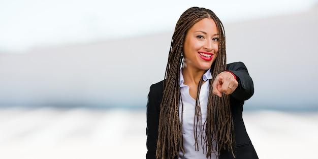 Portrait, de, une, jeune, femme affaires noire, gai, et, sourire, pointant devant