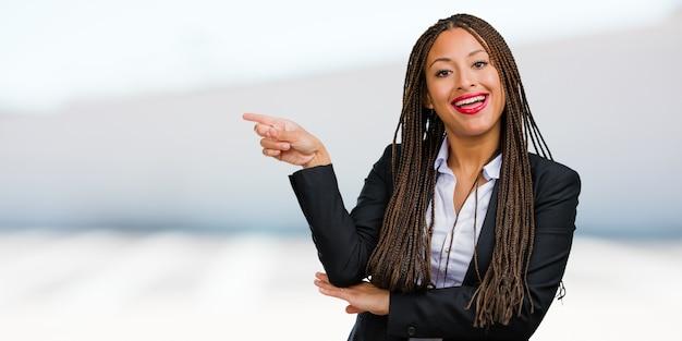 Portrait d'une jeune femme d'affaires noire pointant sur le côté, souriant surpris de présenter quelque chose, naturel et désinvolte
