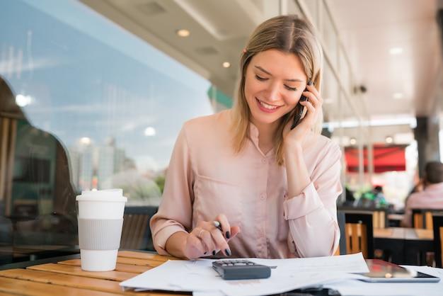 Portrait de jeune femme d'affaires parlant au téléphone tout en travaillant au café. concept d'entreprise.