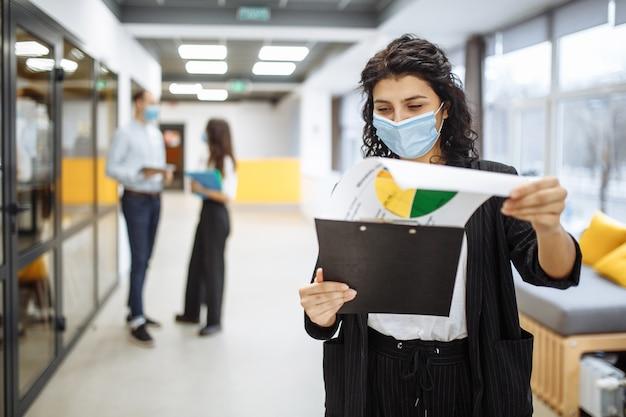Portrait d'une jeune femme d'affaires portant un masque médical vérifiant les papiers et les tendances et perspectives commerciales dans un couloir de bureau.