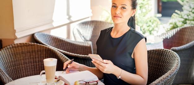 Portrait de jeune femme d'affaires prend des notes dans l'ordinateur portable du smartphone travaillant à la pause-café au café