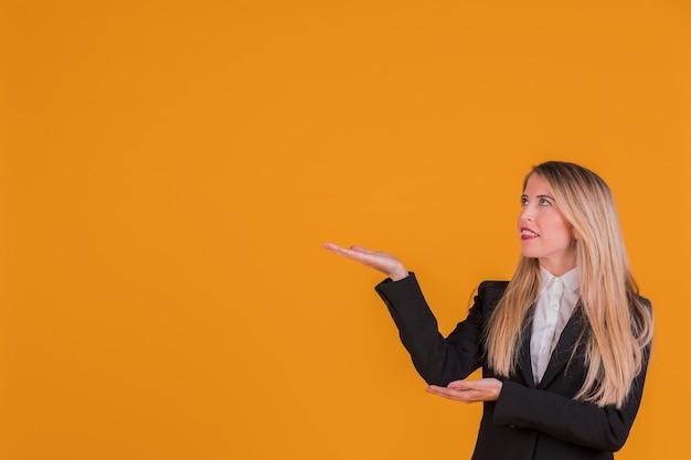 Portrait, jeune, femme affaires, présenter, quelque chose, contre, orange, toile de fond