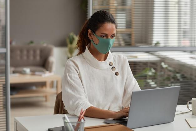 Portrait de jeune femme d'affaires prospère portant un masque tout en utilisant un ordinateur portable et travaillant au bureau au bureau, copiez l'espace