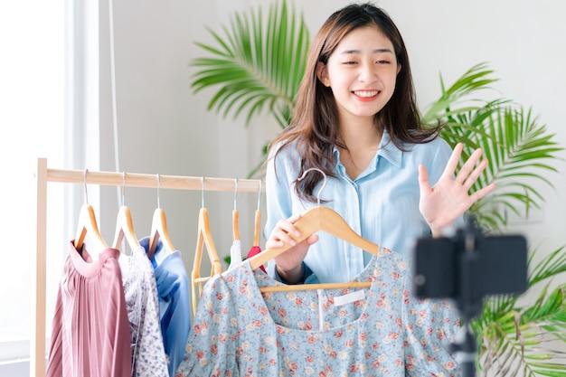 Portrait d'une jeune femme d'affaires qui diffuse des vêtements de vente en direct