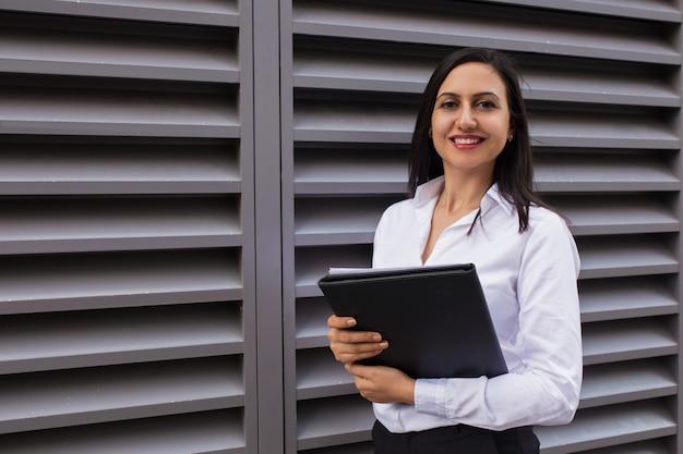 Portrait de jeune femme d'affaires réussie debout avec dossier