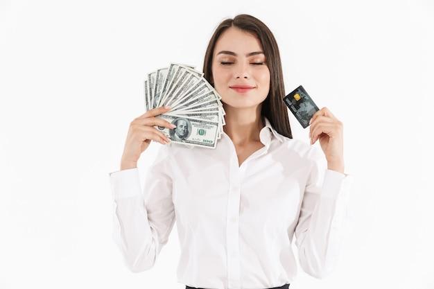 Portrait d'une jeune femme d'affaires séduisante portant des vêtements formels isolés sur un mur blanc, montrant des billets de banque en argent et une carte de crédit