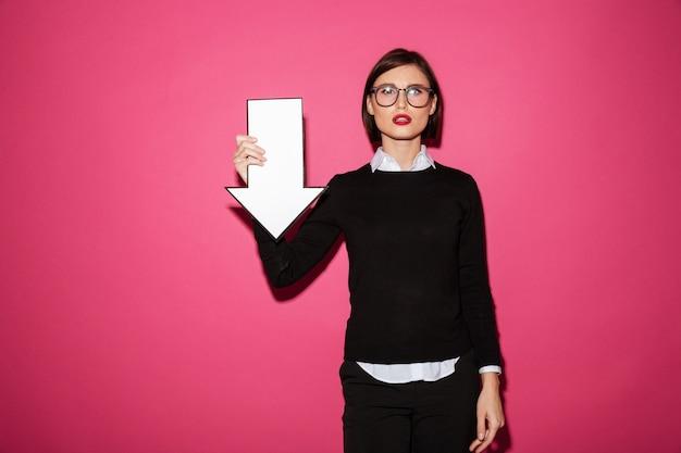 Portrait d'une jeune femme d'affaires sérieuse avec flèche pointant vers le bas