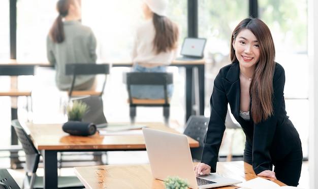 Portrait de jeune femme d'affaires souriant et regardant la caméra tout en se tenant à son bureau et en travaillant avec un ordinateur portable
