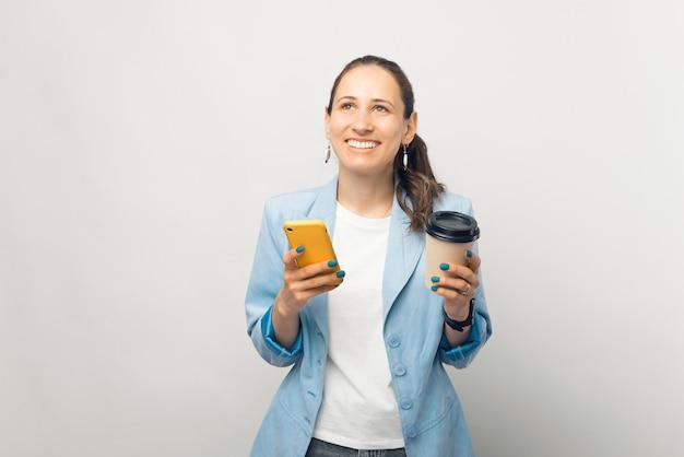 Portrait d'une jeune femme d'affaires souriante et gaie en veste bleue tenant un café pour aller et utilisant un smartphone