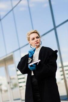 Portrait d'une jeune femme d'affaires avec téléphone, ordinateur portable, tablette, café à l'extérieur. fille blonde en gants bleus en caoutchouc.
