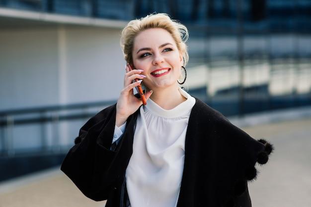 Portrait d'une jeune femme d'affaires avec téléphone, ordinateur portable, tablette, café en plein air. fille blonde en gants de caoutchouc bleu.